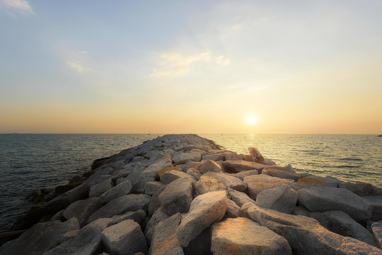 Sunset on the rocky shore of a tropical beach photo