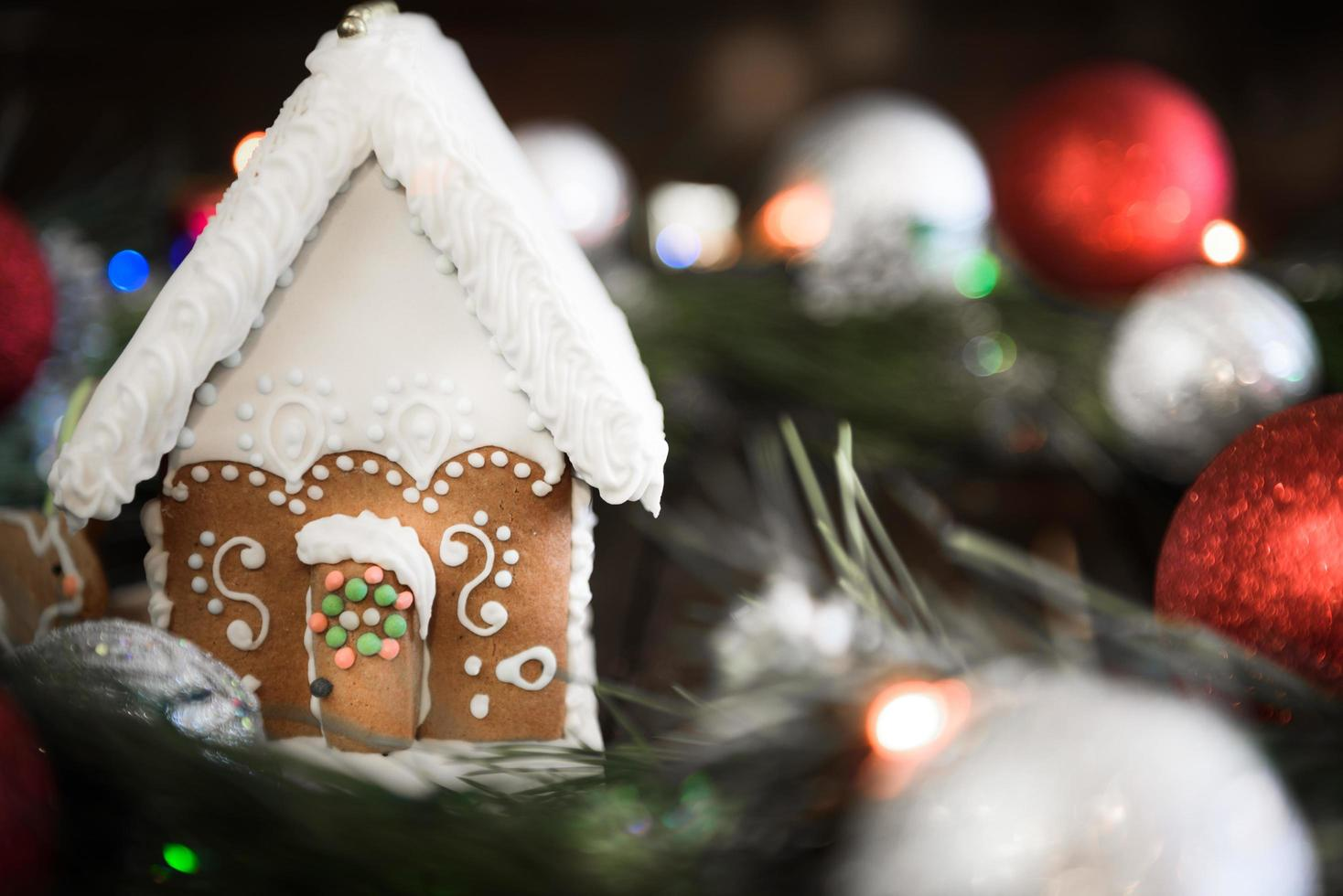Gingerbread house in the white glaze on the background of the Christmas decorations photo
