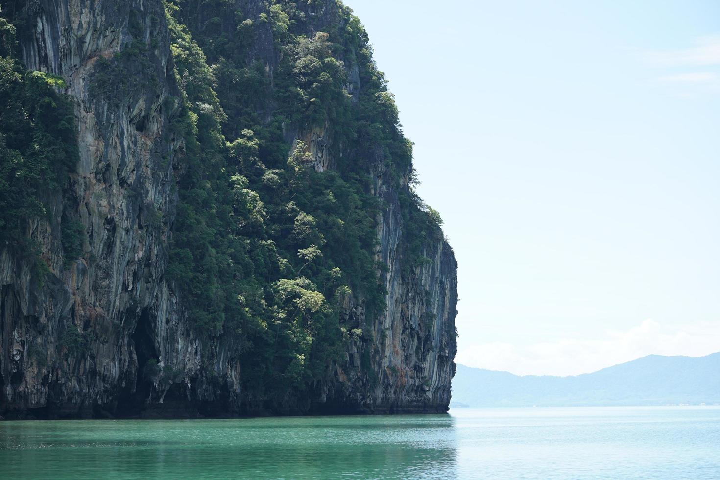 Seascape with trees grow from the mountain cliff on sunny day photo