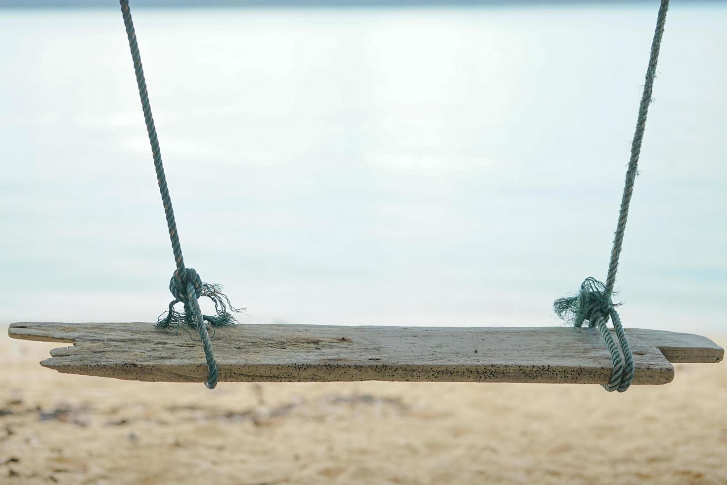 Closeup wooden swing hanging from the tree with old rope and blurred sand in background photo