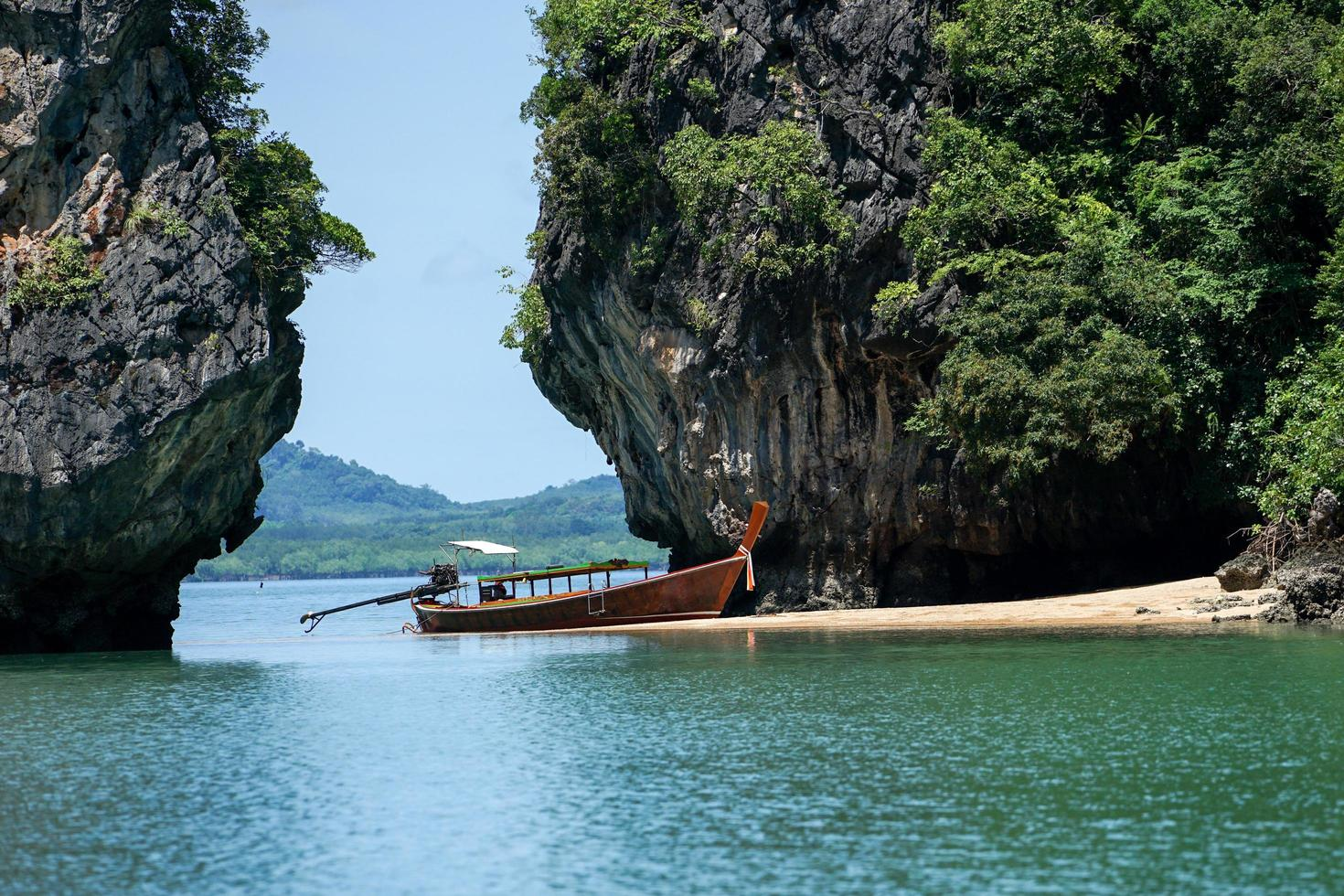 Traditional long-tail boat parks on the beach with high cliff and seascape in background photo
