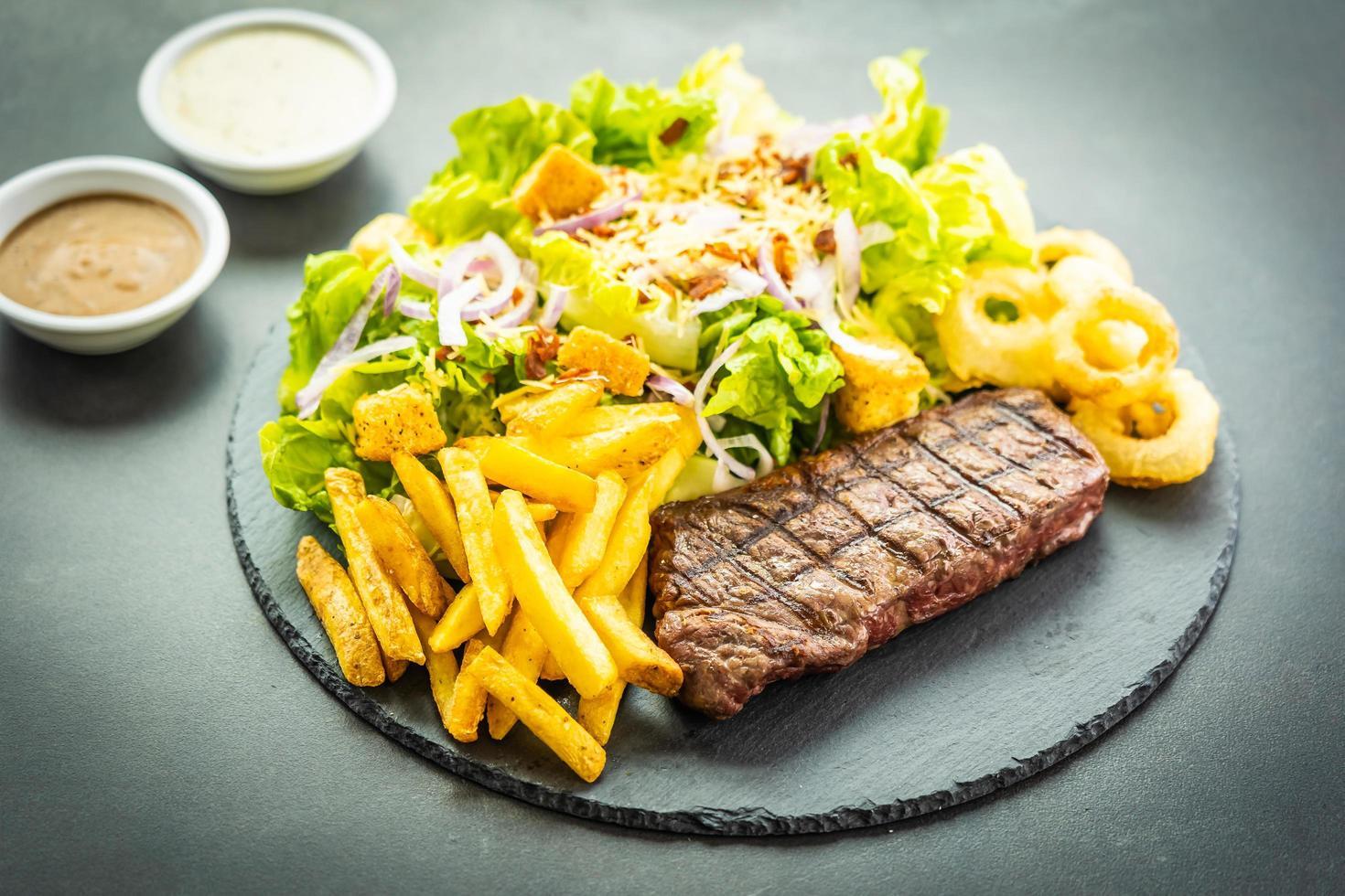 Filete de carne de ternera a la parrilla con patatas fritas aro de cebolla con salsa y verduras frescas foto