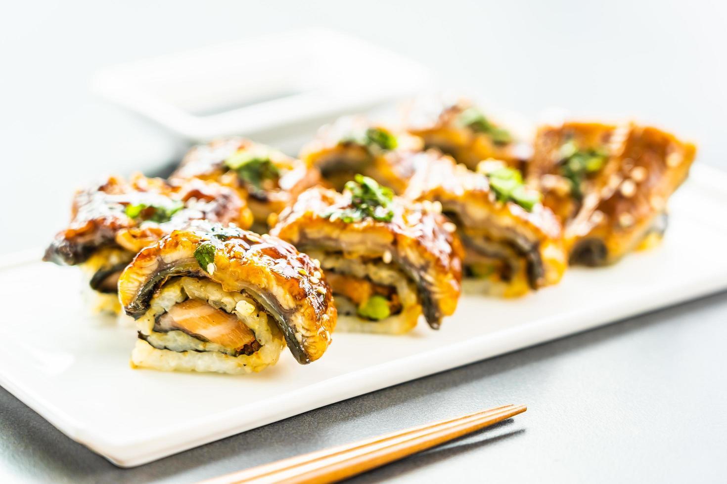 Rollo de maki de sushi de anguila a la parrilla o pescado unagi con salsa dulce foto