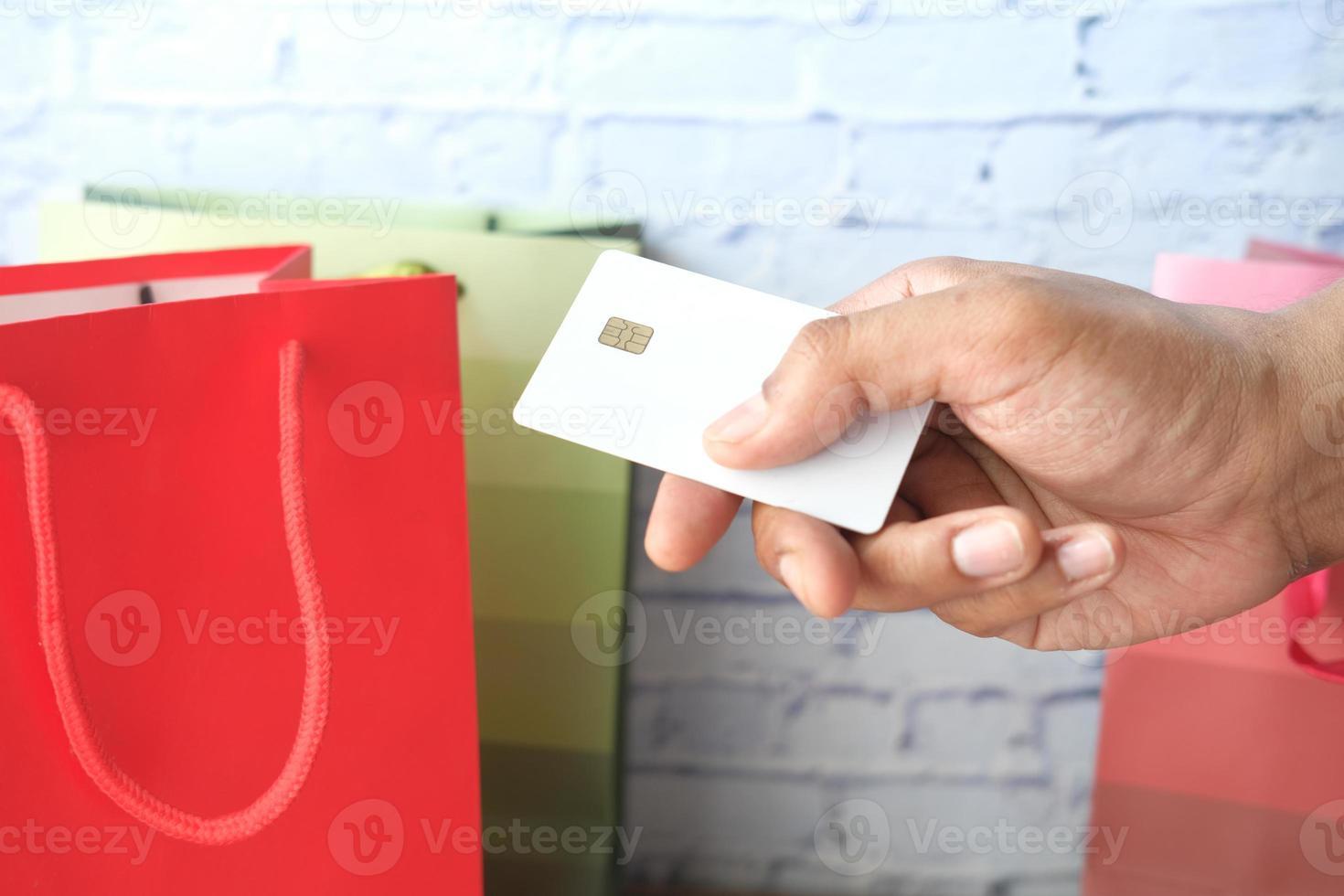 persona que usa una tarjeta de crédito para comprar regalos foto