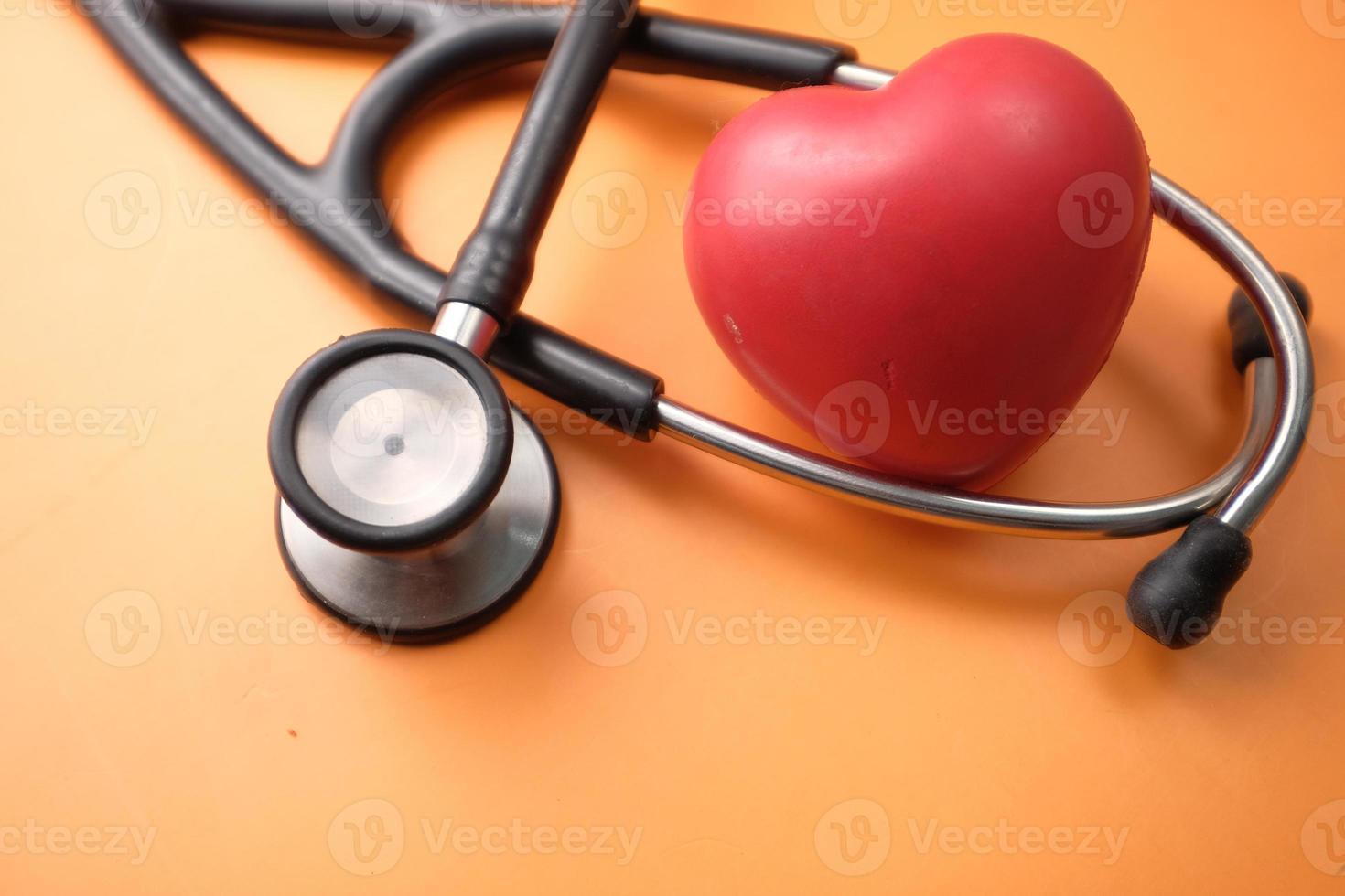Símbolo de forma de corazón y un estetoscopio sobre fondo naranja foto