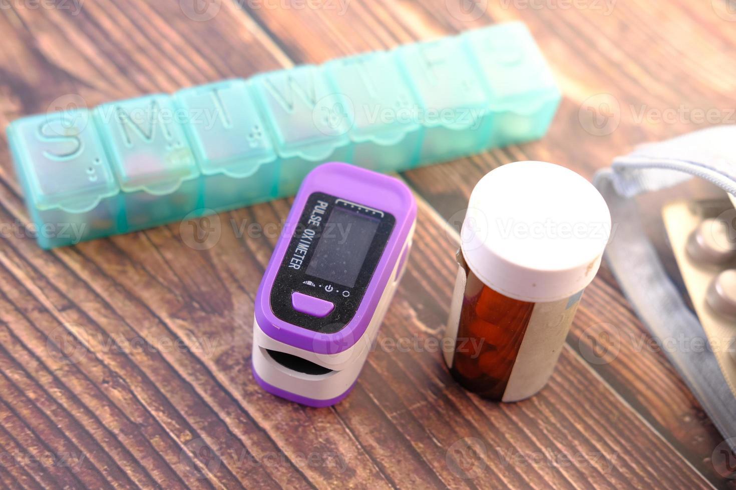 Oxímetro de pulso y contenedor de pastillas en la mesa foto