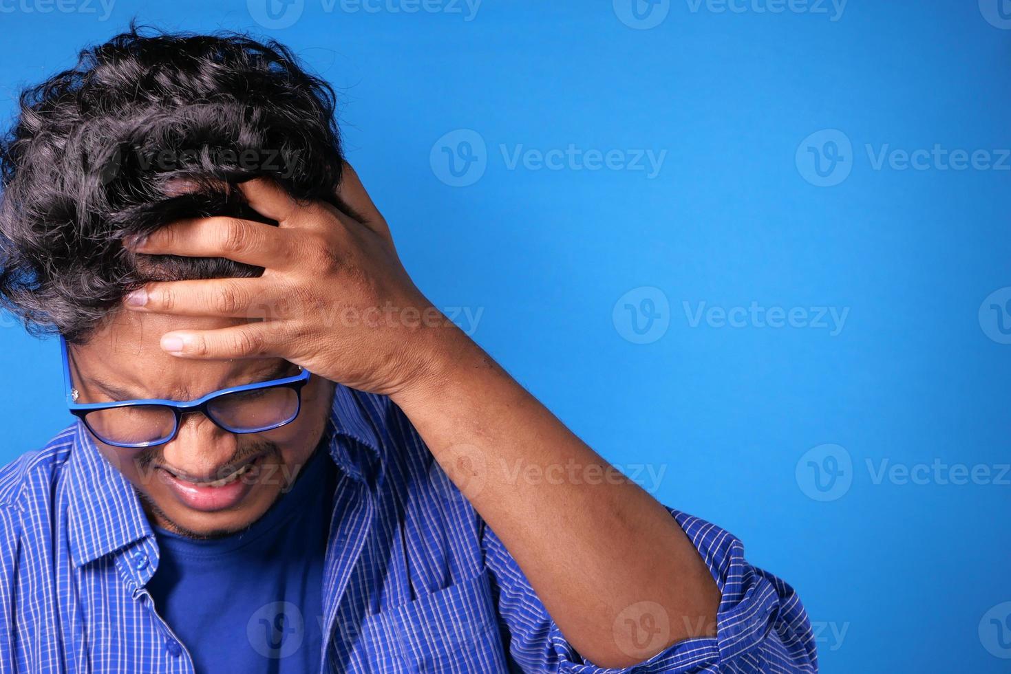Hombre sujetando la cabeza con la mano sobre fondo azul. foto