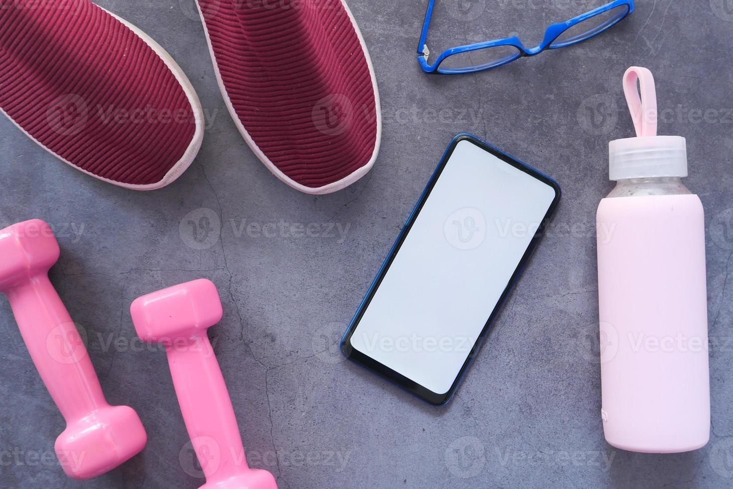 teléfono inteligente con equipamiento deportivo sobre fondo gris foto