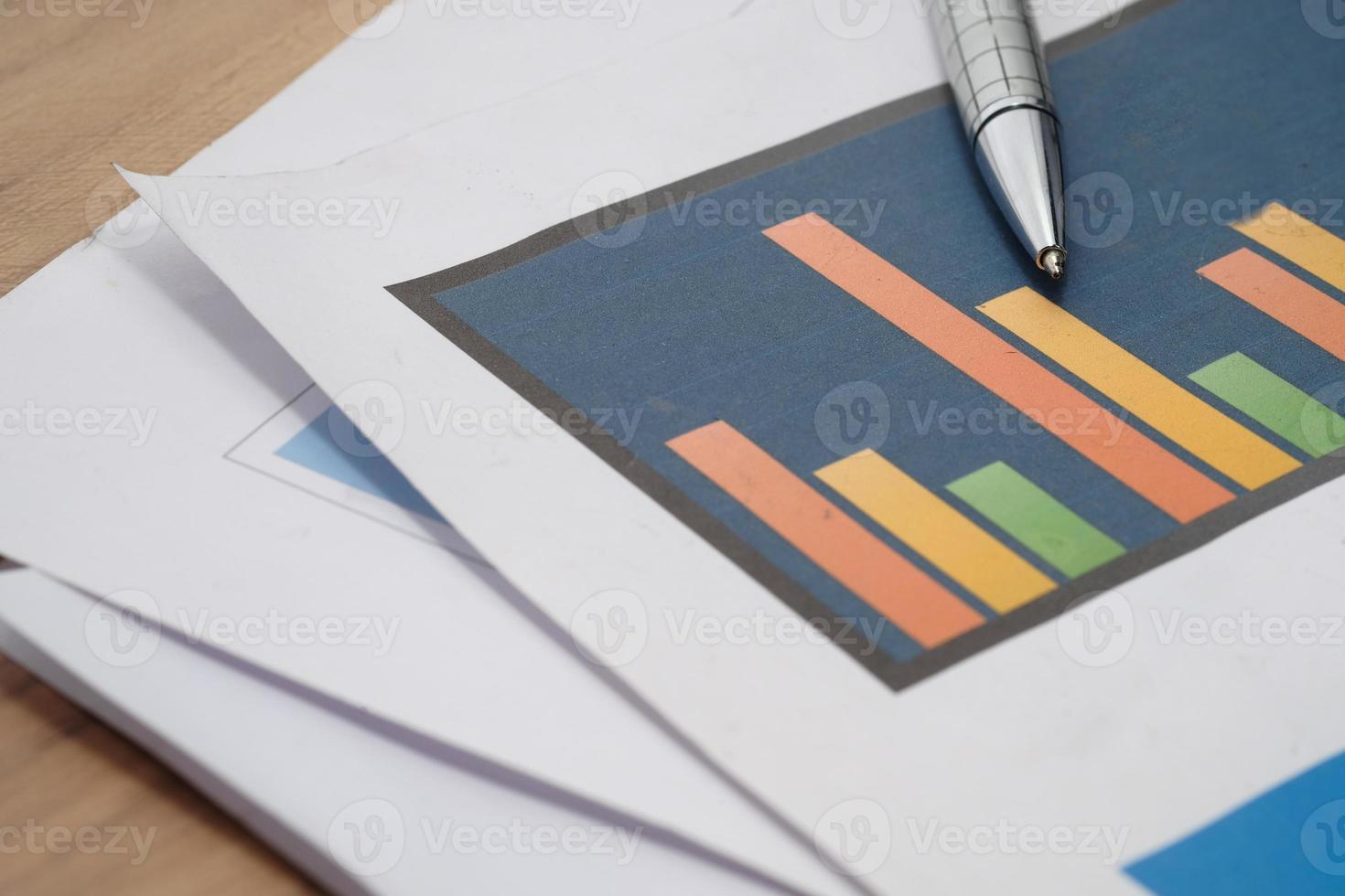 gráficos financieros y bolígrafo en la mesa foto