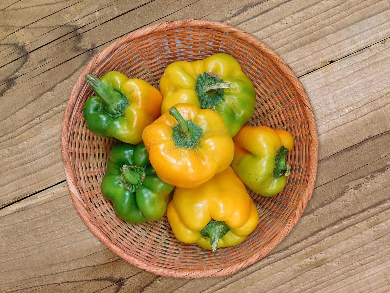 Yellow and green bell peppers in a wicker bowl on a wooden table background photo