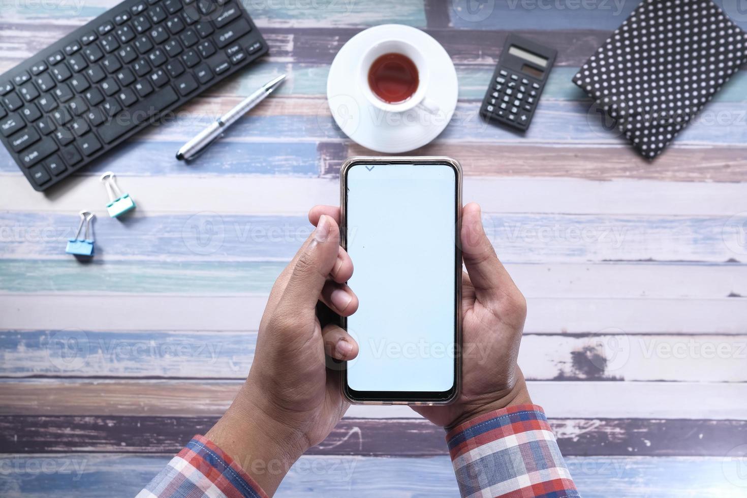 Hand holding smart phone on white background photo