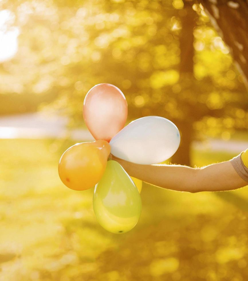 Person holding balloons in sunlight photo