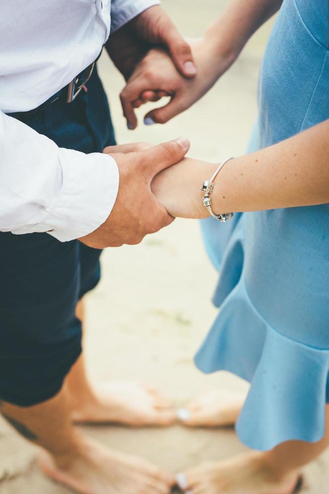 Couple holding hands on a beach photo