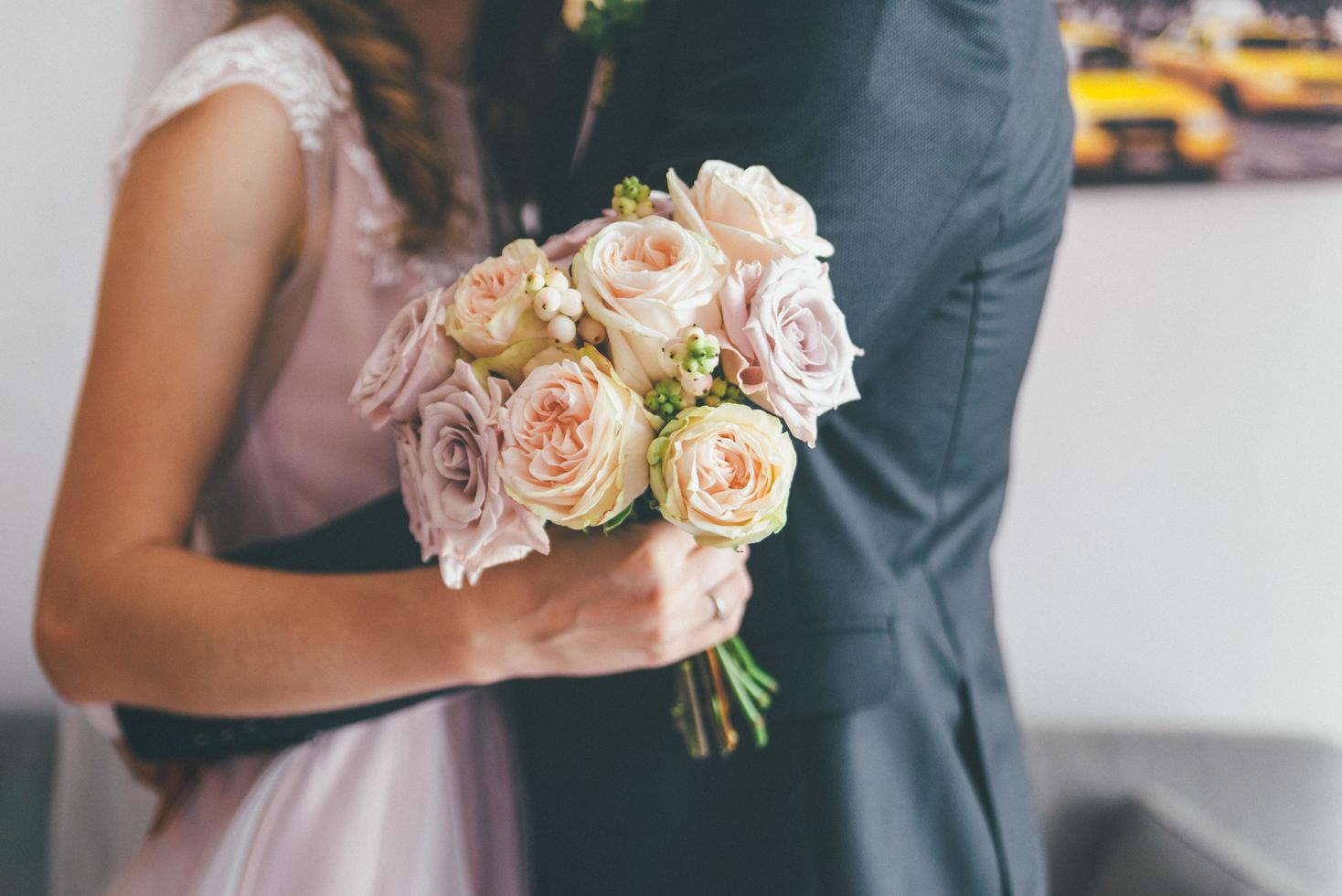 Married couple hugging and holding flowers photo
