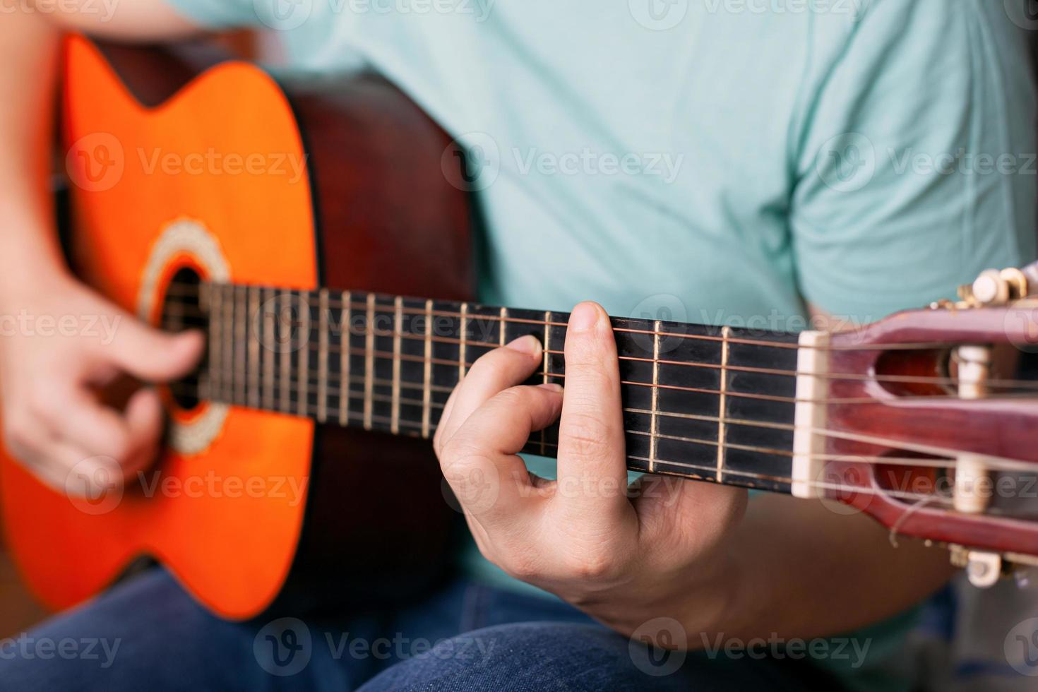 Guy plays acoustic guitar, finger holds a bar chord photo