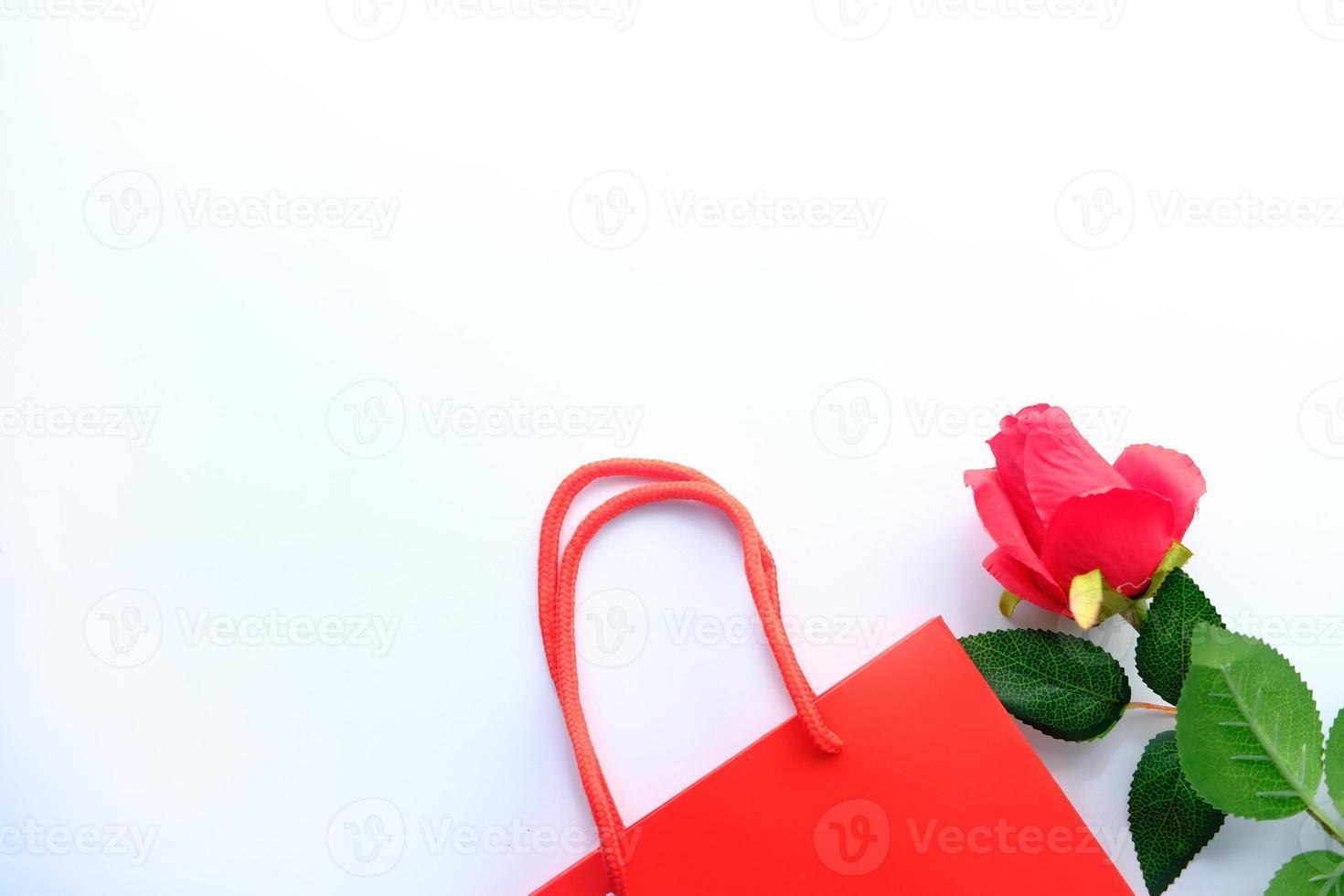 Vista superior de la caja de regalo y flor rosa sobre fondo blanco. foto