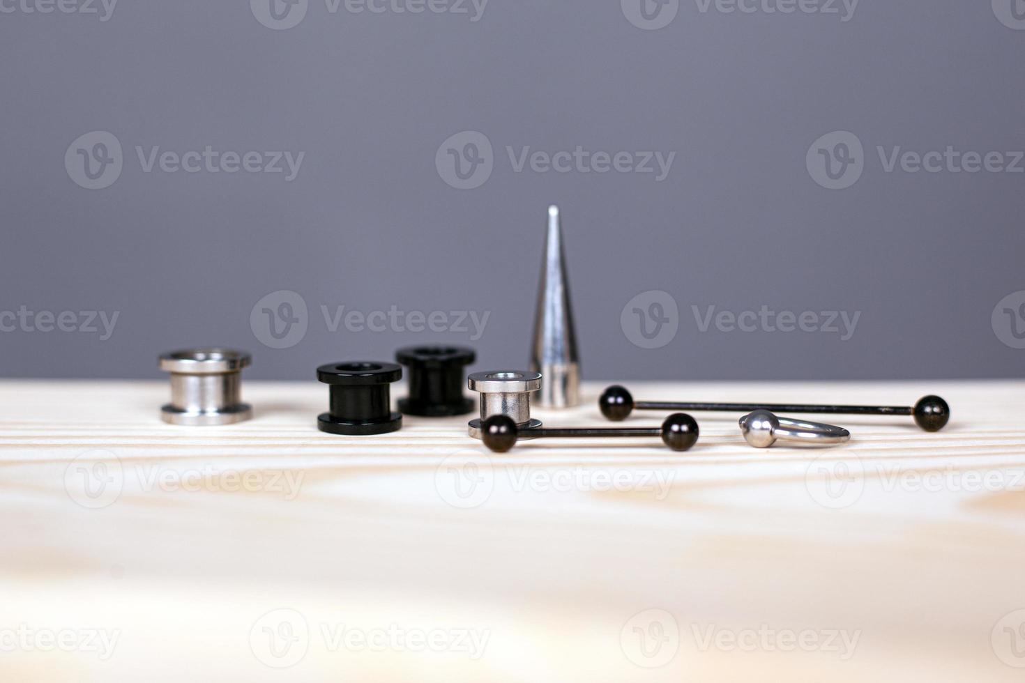 Conjunto de accesorios para perforar la oreja sobre fondo gris foto
