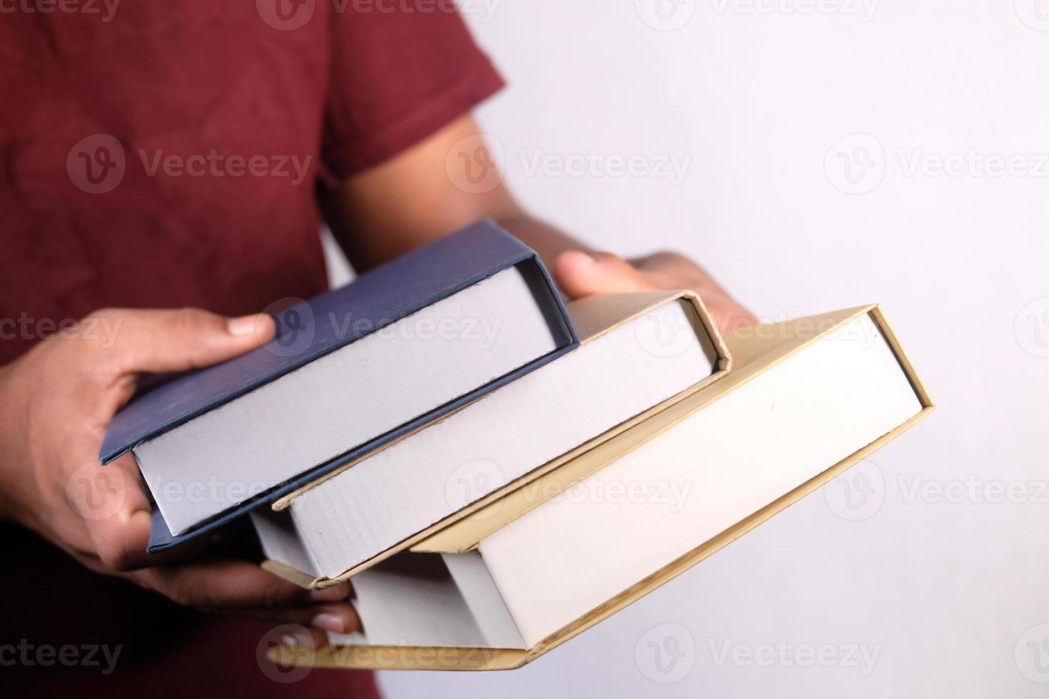 Manos sosteniendo la pila de libros sobre fondo blanco. foto