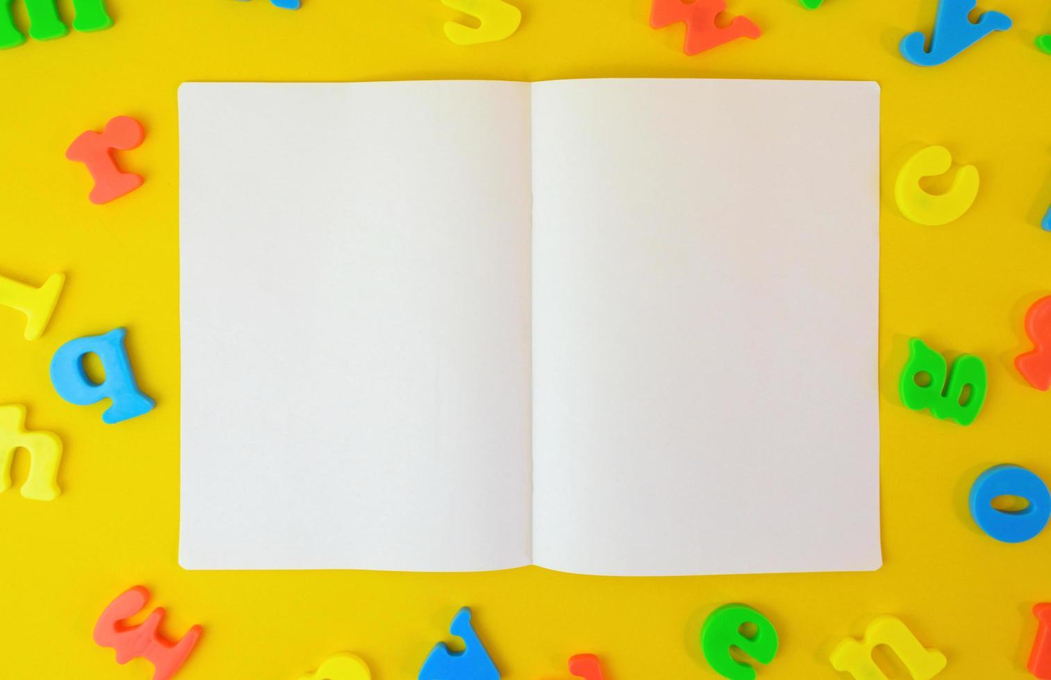 Abrió el cuaderno de dos páginas sobre fondo amarillo cubierto de letras. concepto de educación. Copie el papel del espacio para fotos y mensajes de texto.
