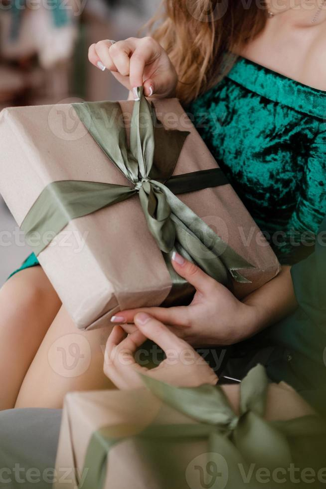 niña sosteniendo un regalo en las manos, mujeres con caja de regalo en las manos envueltas en papel artesanal decorativo con un lazo de cinta verde atado, vista superior, concepto de vacaciones, amor y cuidado foto