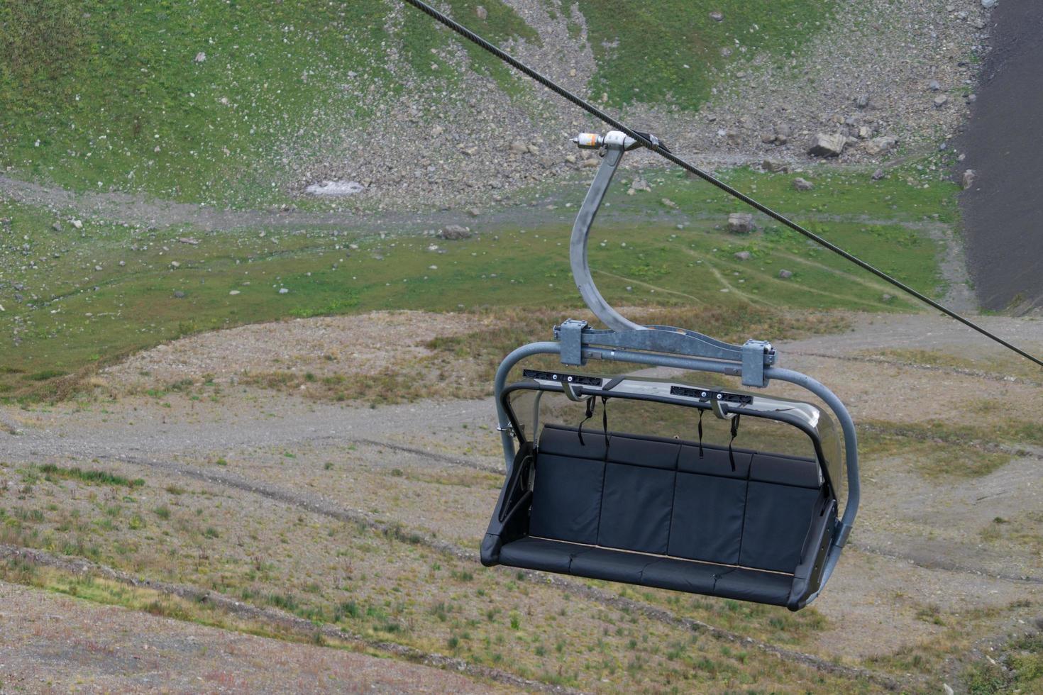 Silla de elevación de esquí en un cable con la montaña en el fondo en Sochi, Rusia foto