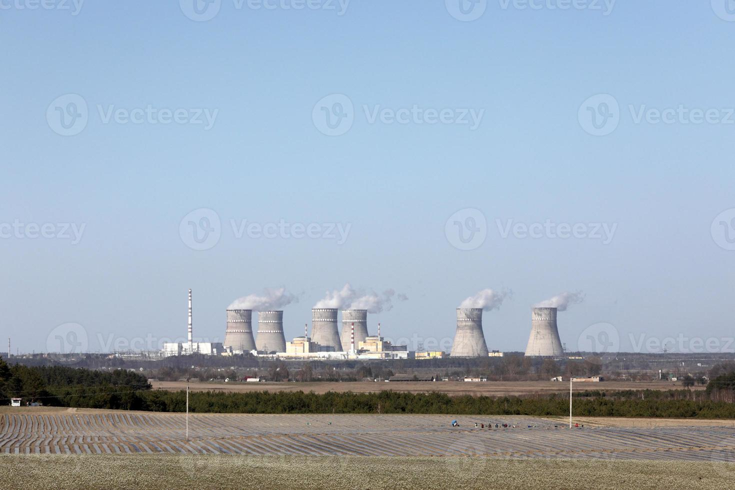 View of a nuclear power plant. View of smoking chimneys of a nuclear power plant, power lines, and forest, under blue sky with white clouds. photo