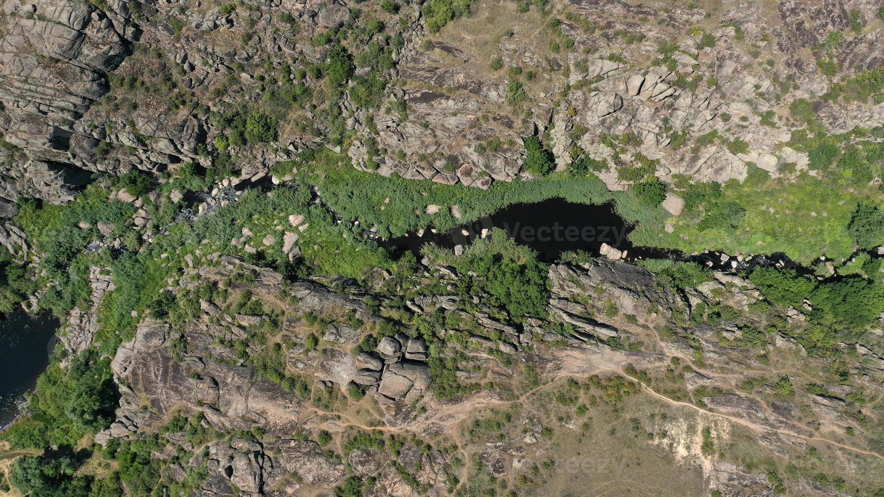 Aerial view of the textures and patterns of the rocks and mountain river with rifts and green photo