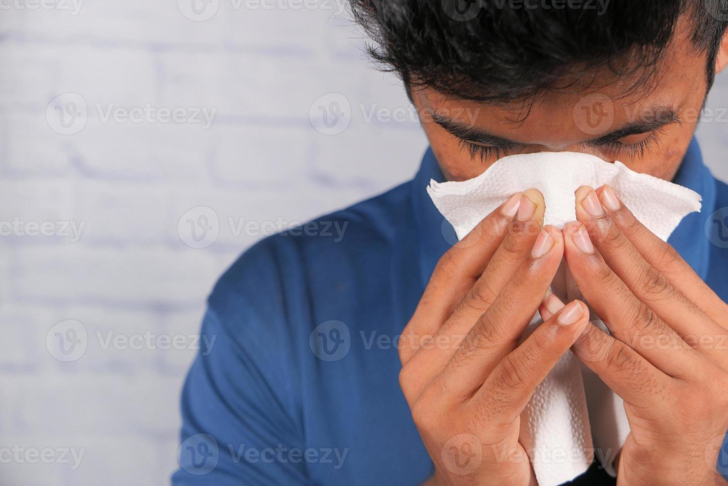 Man blowing his nose photo