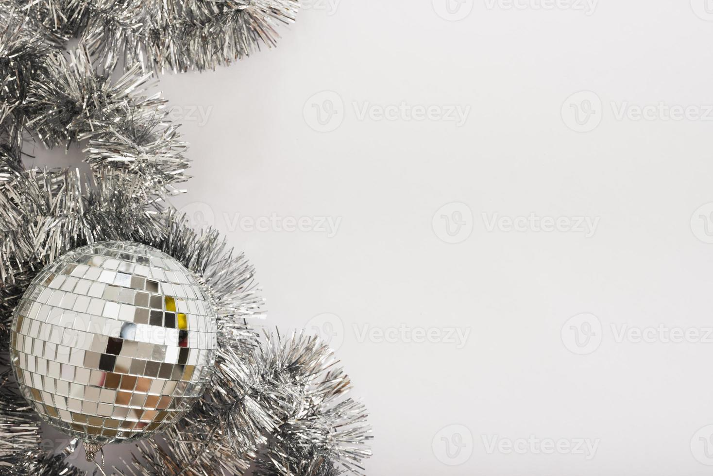 Bola de discoteca con oropel sobre mesa blanca foto