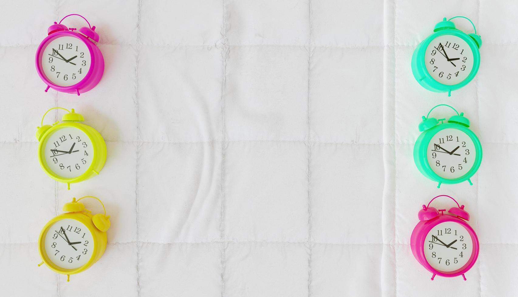 Despertadores de color pastel a los lados de una cama, representación 3D foto