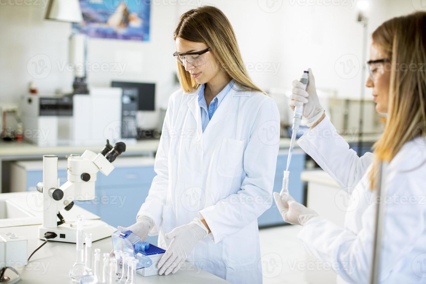 Investigadoras en bata blanca trabajando en el laboratorio. foto