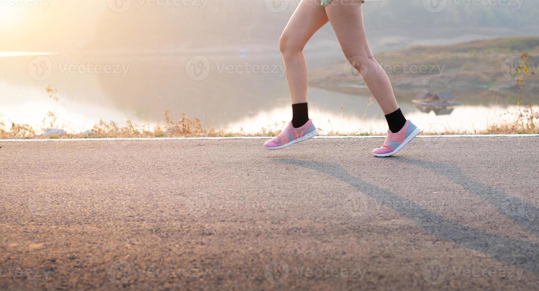mujer joven, llevando, calzado deportivo, funcionamiento, en, asfalto, camino foto