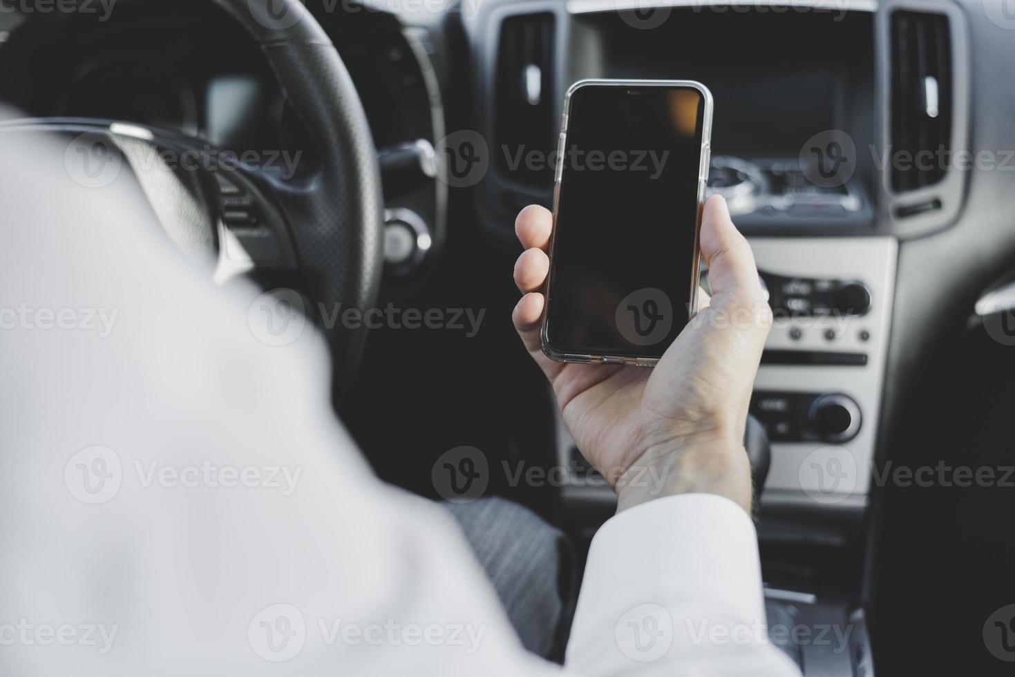 Primer plano de la mano del hombre que sostiene el teléfono móvil con pantalla en blanco en el coche foto