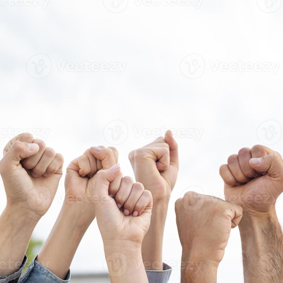 Grupo de activistas sosteniendo los puños sobre fondo blanco. foto