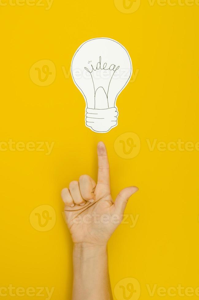 Mano apuntando a la bombilla sobre fondo amarillo foto