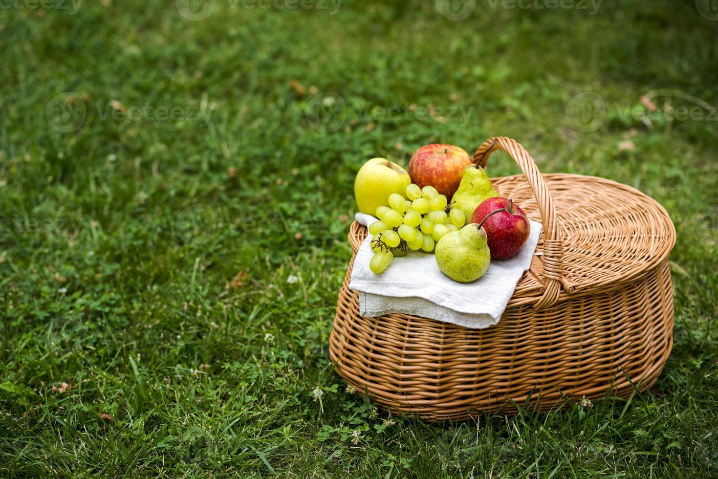Cesta de picnic de ángulo alto con frutas sobre la hierba verde foto