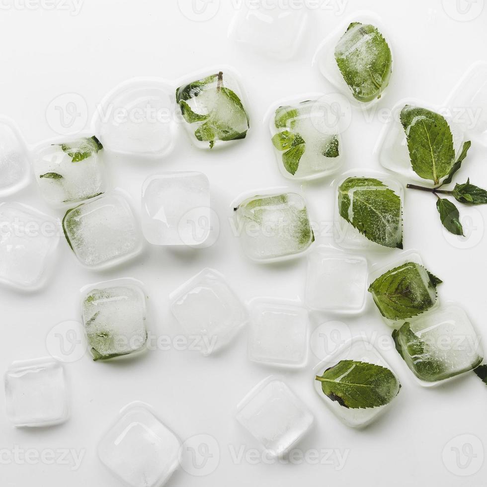 cubitos de hielo y hojas verdes en la mesa blanca foto
