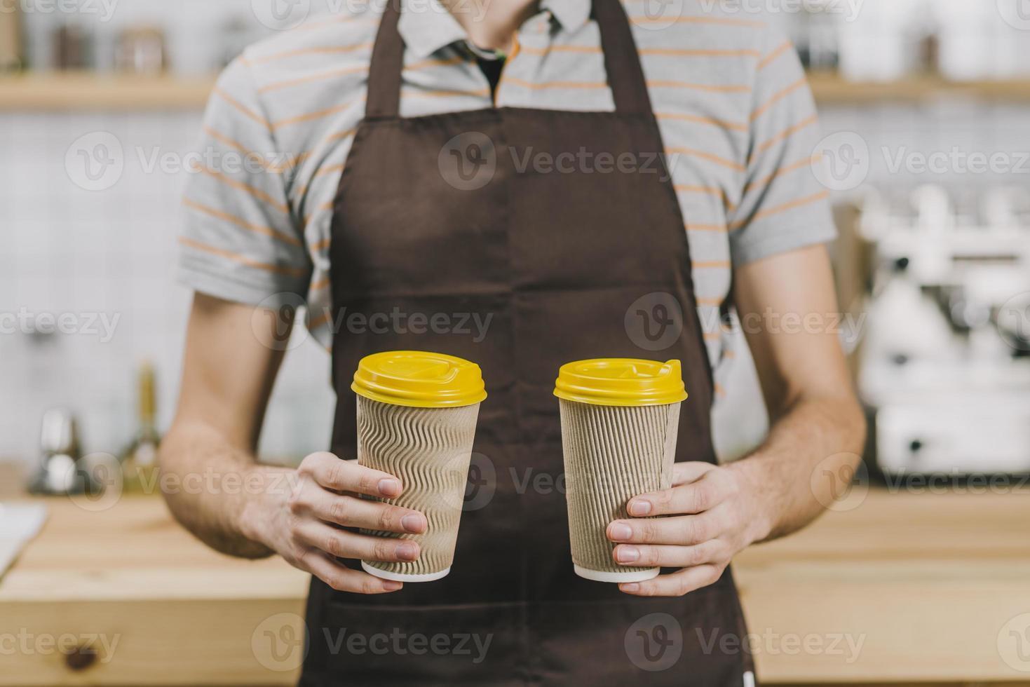 barista recortada con bebidas calientes frente a la cámara foto