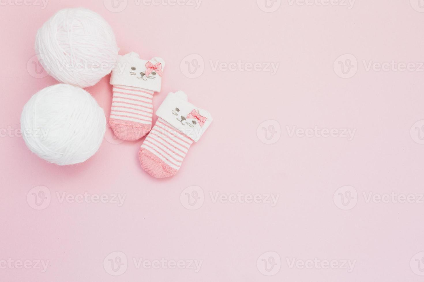 lindos calcetines de lana minúsculos sobre fondo rosa foto