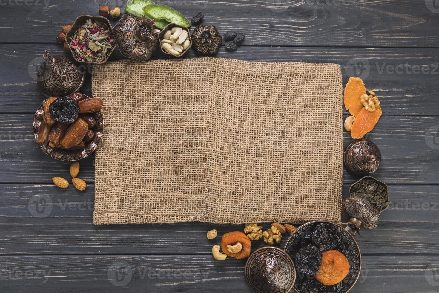 Diferentes frutos secos con nueces bordeando el lienzo sobre fondo de madera foto