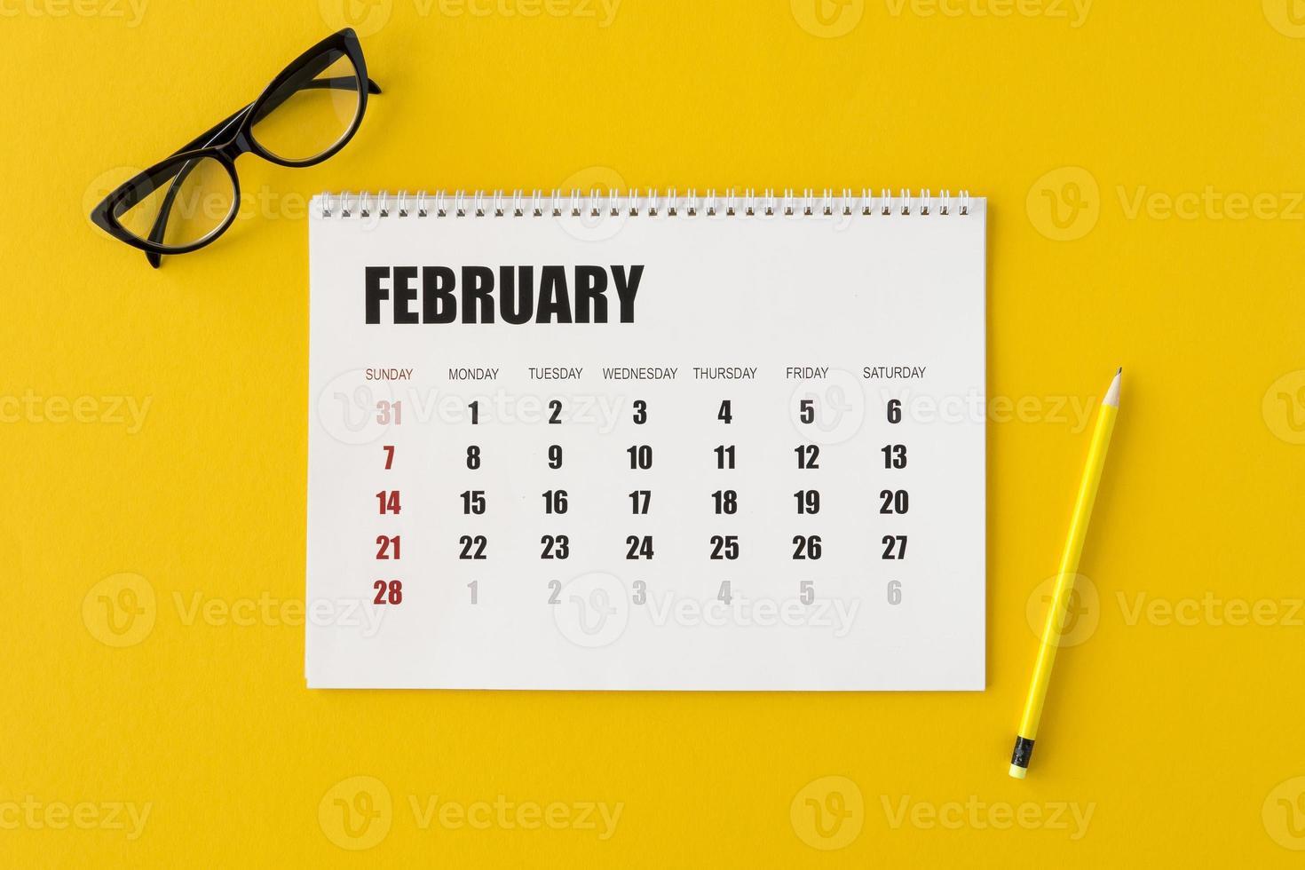 Calendario planificador plano laico sobre fondo amarillo foto