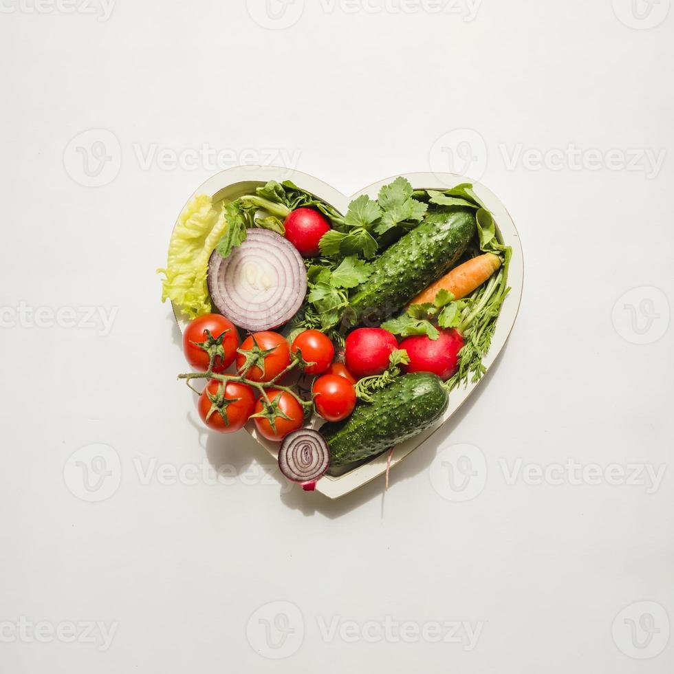 Corazón de diferentes tipos de verduras sobre fondo blanco. foto