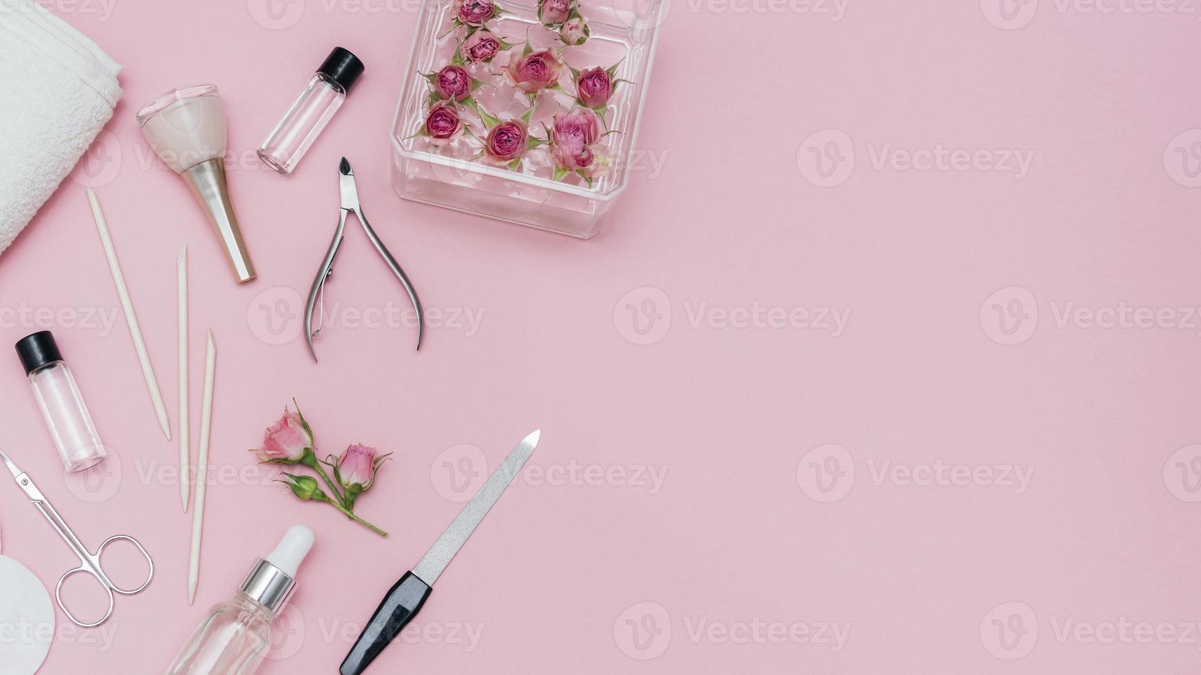 Disposición de accesorios para el cuidado de las uñas sobre fondo rosa. foto