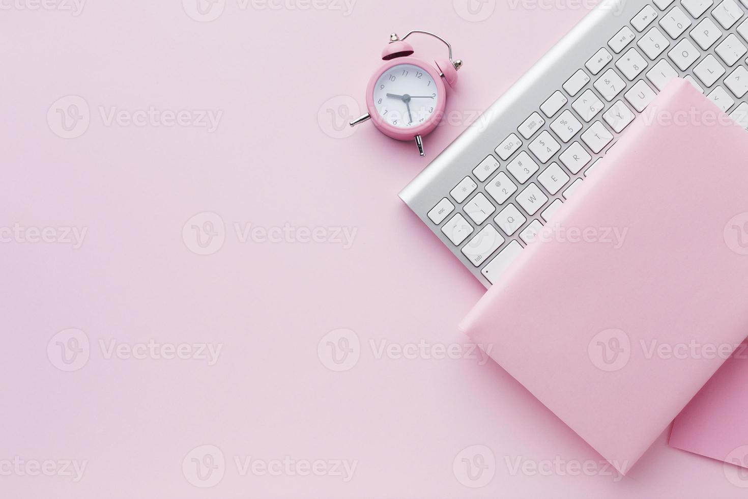 Libro en blanco y teclado con reloj rosa sobre fondo rosa foto