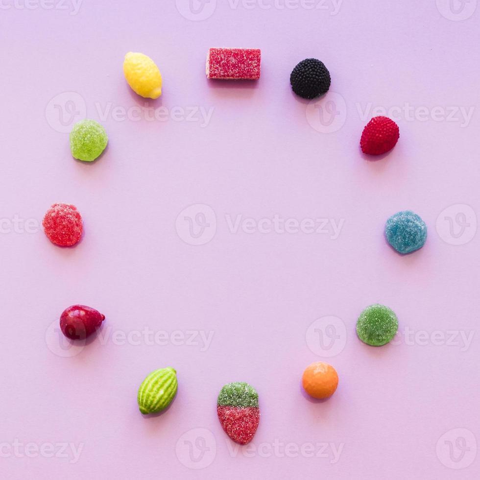 círculo hecho con caramelos de gelatina de azúcar fondo rosa. concepto de fotografía hermosa de alta calidad y resolución foto