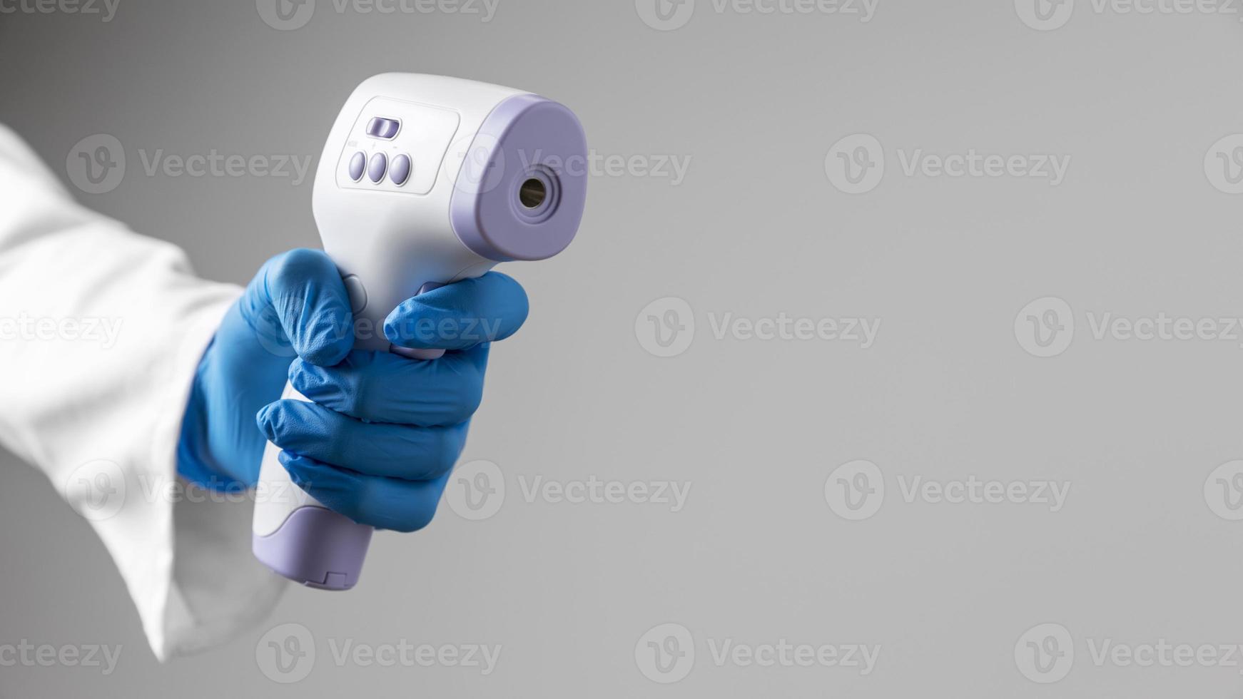 Doctor en guantes tiene termómetro con espacio de copia foto