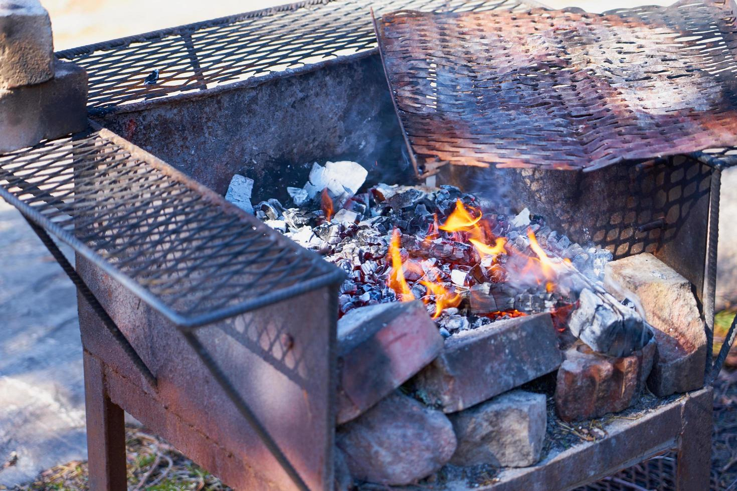 Fire in a rusty vintage grill outdoor with blurred background photo