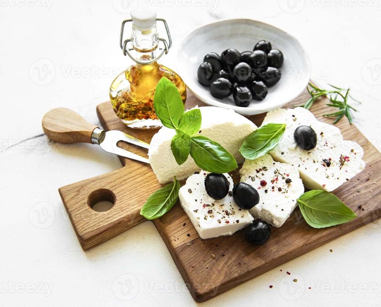 Fresh ricotta with basil leaves and olives photo