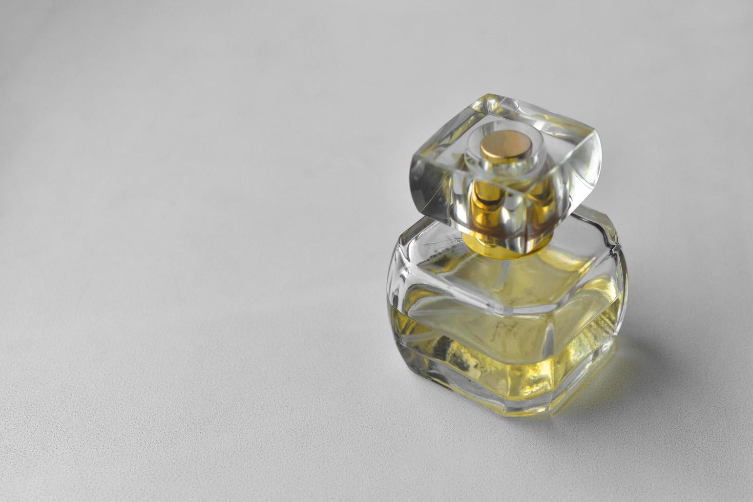 Frasco de perfume amarillo sobre un fondo blanco. foto