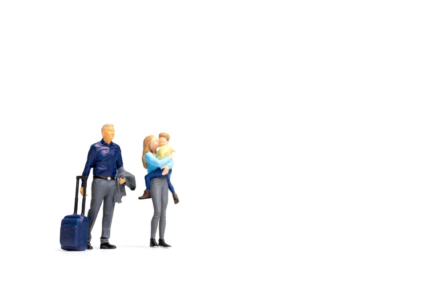Gente en miniatura, familia feliz de pie sobre un fondo blanco y espacio para copiar texto foto